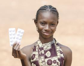A girl holds up medication. Photo credit- iStock.