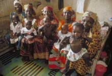 Source - MLE/NURHI. Description - Group of mothers waiting with their children in the waiting room of a public health facility in Nigeria.